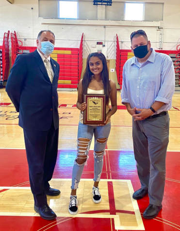Mr. Ross, Krystal, and Mr. Sandaal posing for a picture with the scholar athlete plaque after the virtual winter varsity awards night.  Photo Credit: Ms. OBoyle